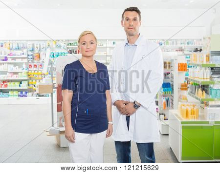 Confident Assistant And Pharmacist Standing In Pharmacy