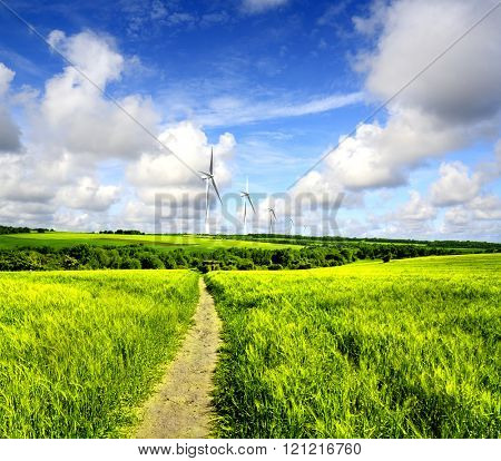 Wind turbines farm in field over cloudy sky