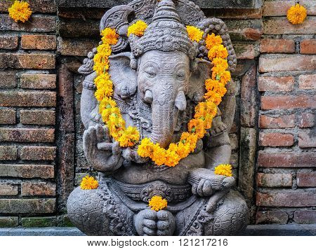 Hindu god Ganisha with yellow flowers