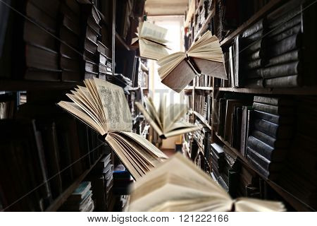 Flying books on library bookshelves background