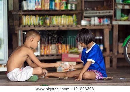 AO YAI, THAILAND, JANUARY 30, 2016 : Two little boys sitting on a floor in a store are playing  roshambo rock paper scissor game in the Ao Yai fishing village, Ko Kood island, Thailand