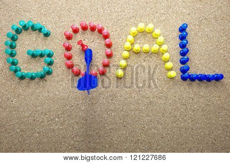 Colorful push pins and blue dart with