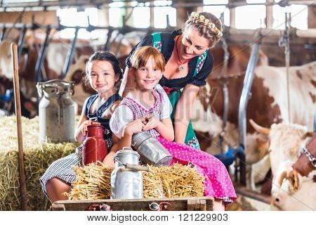 Bavarian mother driving children on pushcart with hay bale through cowhouse