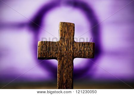 closeup of the blurry holy cross and the crown of thorns of Jesus Christ in the background against a rustic wooden surface