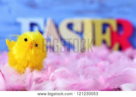 closeup of a yellow toy chick surrounded by soft pink feathers and some three-dimensional letters forming the word easter in the background, against a blue background