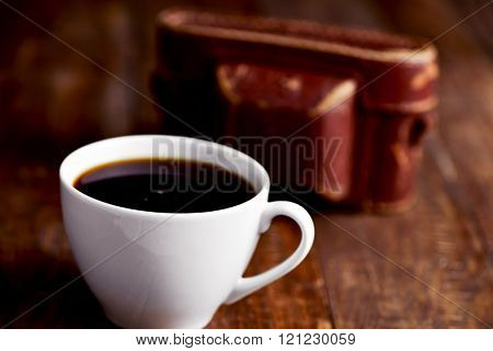closeup of a cup of coffee and an old camera in its case on a rustic wooden surface