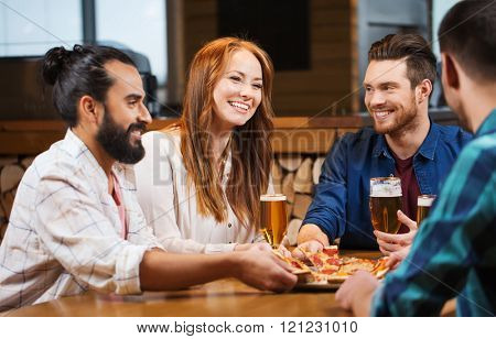 leisure, food and drinks, people and holidays concept - smiling friends eating pizza and drinking beer at pizzeria or pub
