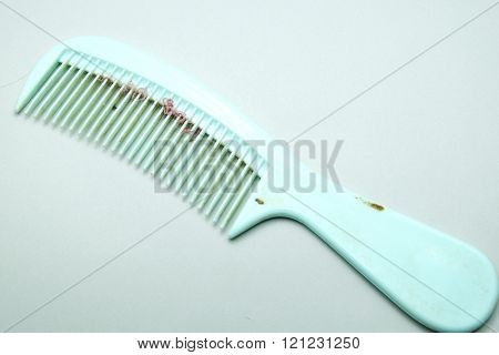 Old and dirty green comb on gray background.