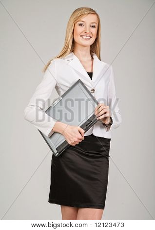 Beautiful blonde businesswoman holding laptop