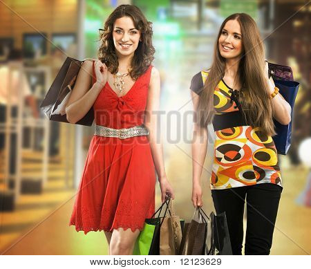 Two beautiful young women at a shopping mall with bags
