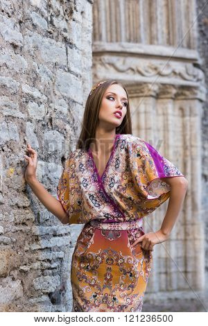 Gorgeous elegant girl in ethnic dress leaning on antique wall in summer.
