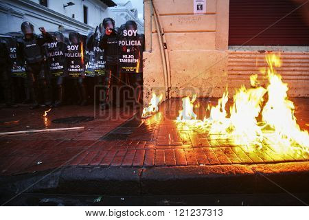 Quito, Ecuador - August 27, 2015: Sidewalk on fire during violent protests, large group of riot poli