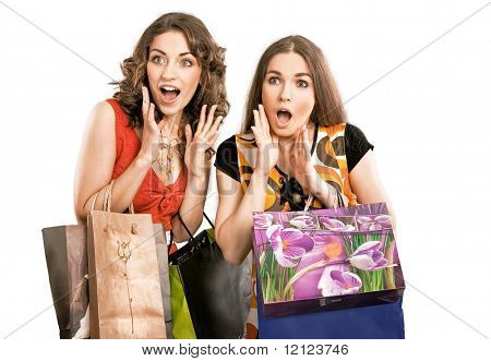 Two astonished girls on shopping trip, isolated on white