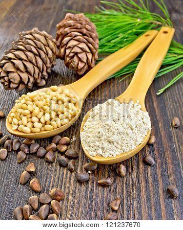 Flour and nuts cedar in spoon on board