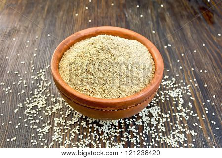 Flour sesame in clay bowl on board