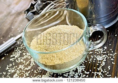 Flour sesame in cup with sieve on board
