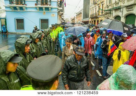 Quito, Ecuador - August 27, 2015: Protesters walking through city streets with umbrellas  passing ro