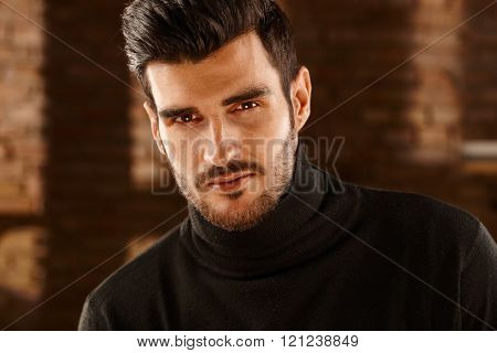 Closeup portrait of handsome young man looking at camera in turtleneck pullover.
