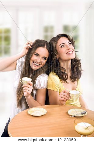 Two beautiful women drinking coffee and chatting