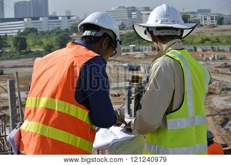 SELANGOR, MALAYSIA - MAY 15, 2014: Construction workers referring to the construction drawing plans at the construction site at Selangor, Malaysia.