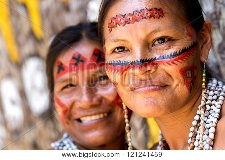 Native Brazilian women smiling at an indigenous tribe in the Amazon
