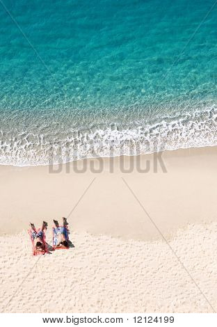 View of two people lying on tropical beach, lots of copyspace