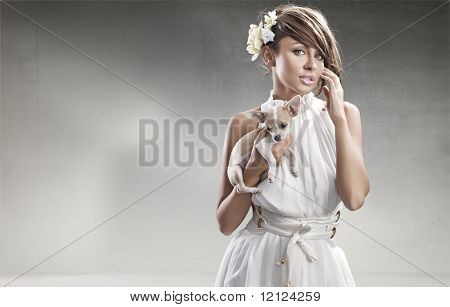 Elegant woman holding a small dog