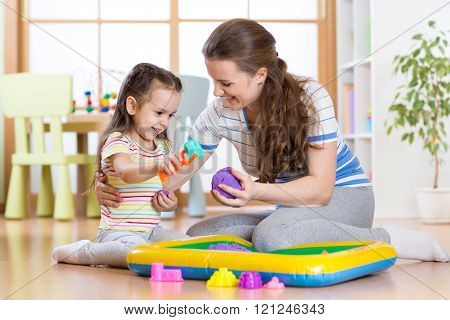 Child little girl and mother playing with kinetic sand at home
