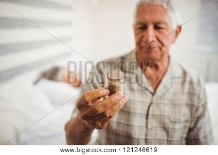 Senior man sitting on bed and looking at a pill bottle
