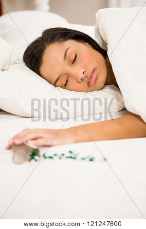 Brunette sleeping in bed by spilt bottle of pills at home