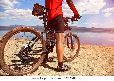 man with bike on a mountain lake