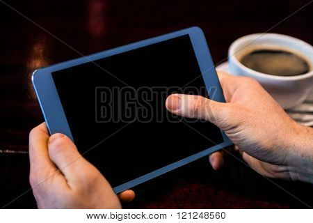 Businessman using tablet having a coffee at the counter in a bar