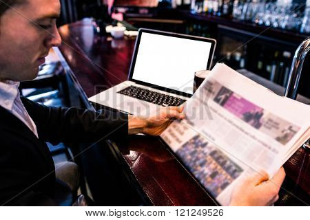 Businessman reading the news and using laptop at the counter in a bar