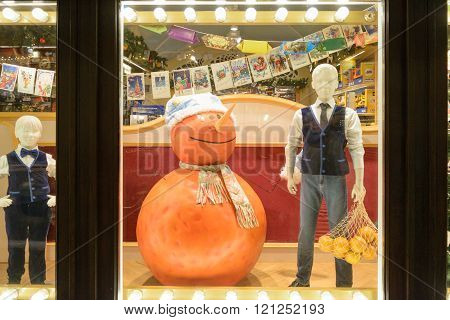 Mannequin Boy With Fruit And Orange Snowman Standing In Shop Window