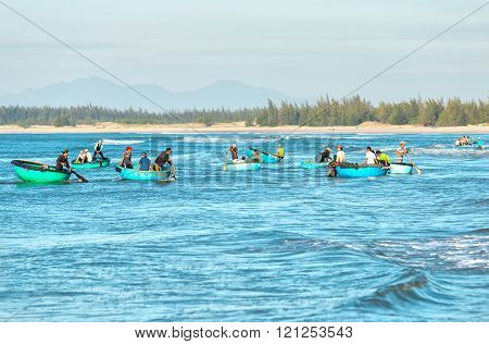 Binh Thuan, Vietnam - January 21st, 2016: Fishermen rowing anchovy transported to shore when the blue sea in the morning at the bustling fishing village of Binh Thuan, Vietnam
