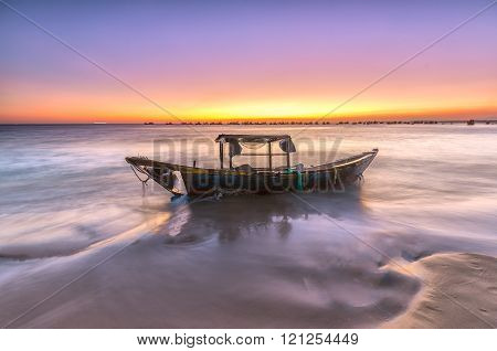 The boat rotting under the purple twilight sky on beautiful beaches while boat mirror into the water floating offshore with colorful sky with purple, pink, gold interwoven to create a beautiful picture of nature