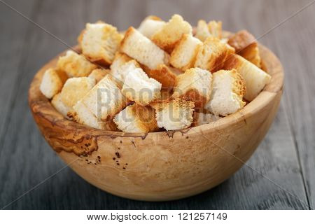 homemade croutons from white bread in wood bowl on oak table