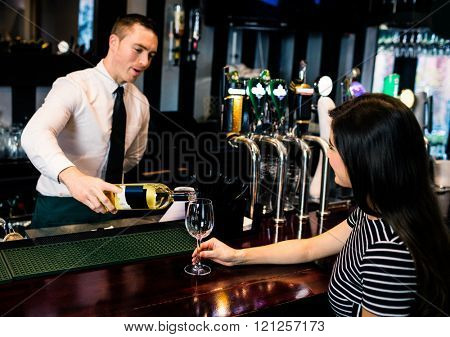 Barman serving a glass of wine in a bar