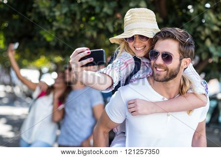 Hip man giving piggy back to his girlfriend and taking selfie on the street