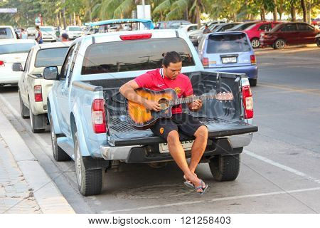 PATTAYA, THAILAND - Dec 30 2011: A man playing guitar on back of truck to entertain tourists, Thaila
