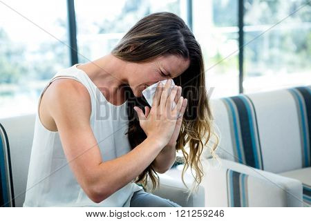 sick woman, sitting on a couch, sneezing into a tissue