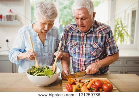 Senior couple preparing salad in kitchen