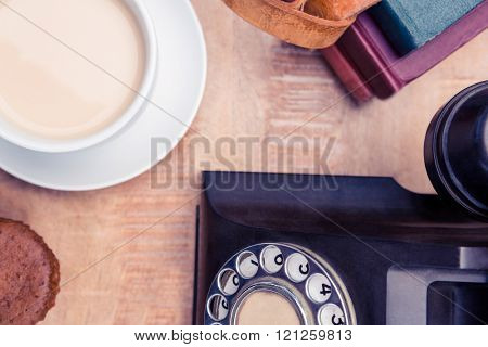 Overhead view of old landline telephone with diaries and coffee on table