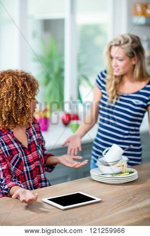 Upset woman showing dirty dishes to friend in kitchen