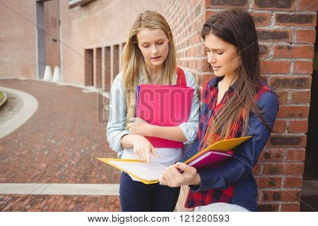 Serious students reading book at university
