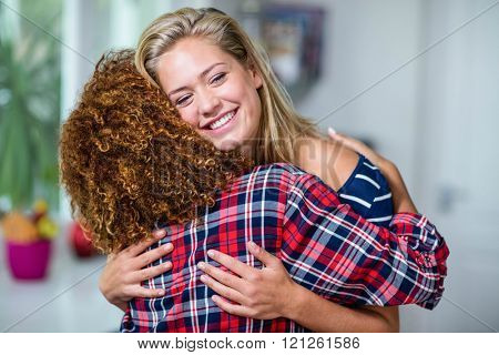 Happy friends hugging in the kitchen