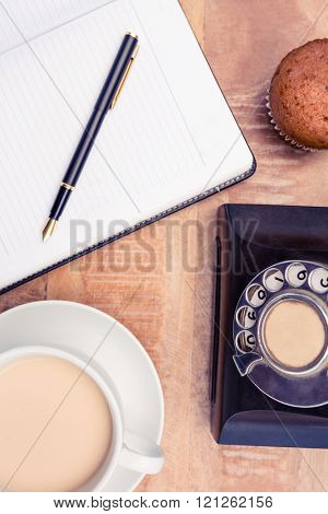 Close-up of coffee with old land line and book on table