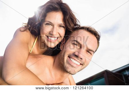Portrait of man giving piggy back to woman near poolside on a sunny day