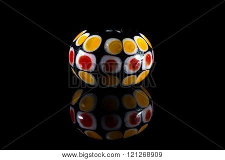 Yellow and red glassy bead with reflection