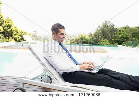 Smarty dressed using laptop near poolside while relaxing on sun lounger